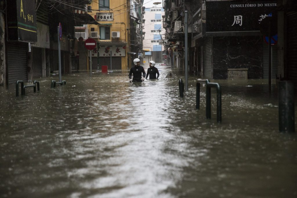 Des policiers dans une rue inondée de Macau